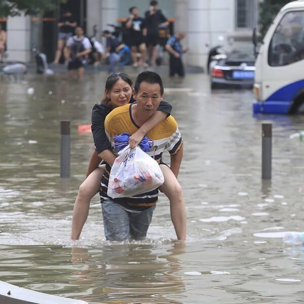 En man bär en kvinna på ryggen i midjehögt vatten på gatan i Kina. Kvinnan är vid medvetande och rynker på näsan. Hon håller i en plastpåse.