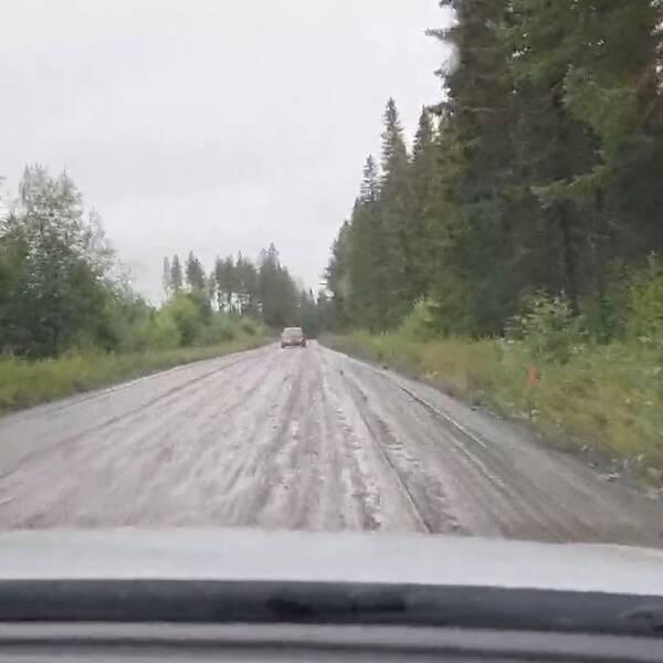 Bil färdas på dålig grusväg i regn.