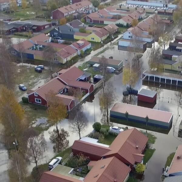 Delad bild. På den vänsta står en man i gul arbetsjacka står med armarna i sidan. På den högra en flygbild över ett bostadsområde med stora vattenmassor mellan husen.