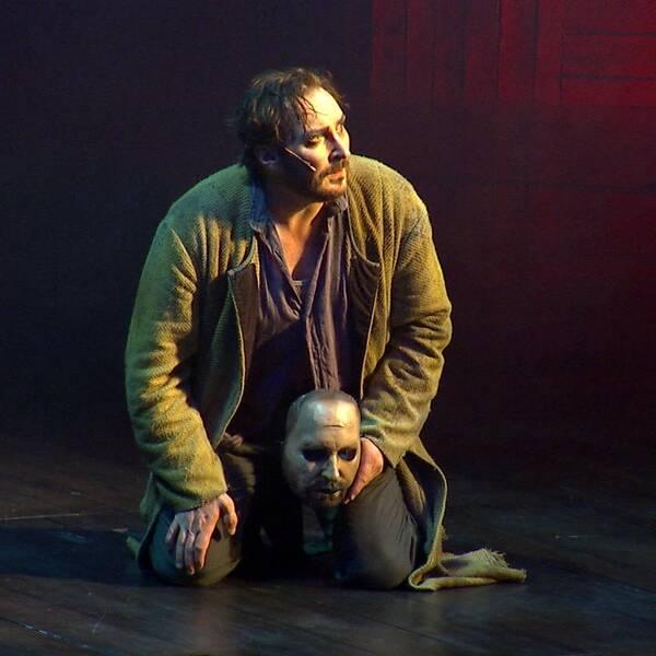 Skådespelaren Jakob Hultcrantz sitter på scen med en ansiktsmask i handen ur föreställningen Körkarlen