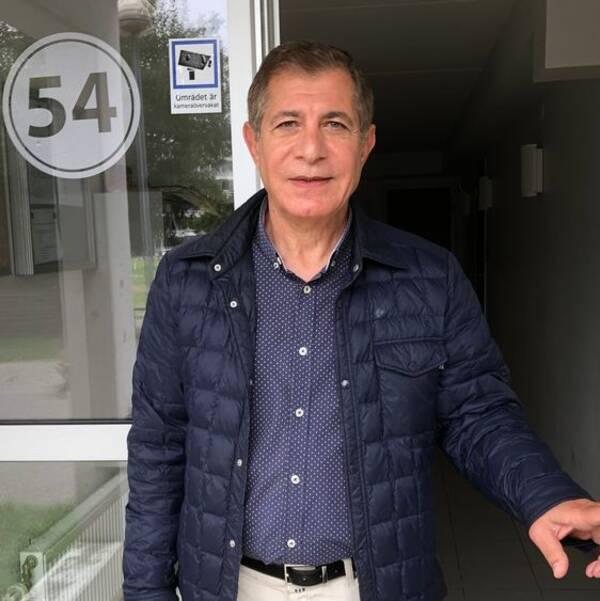 Fuad Al Suheilly står i porten till lägenhetshuset.