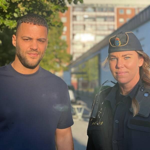 En man och en poliskvinna med höghus i bakgrunden.