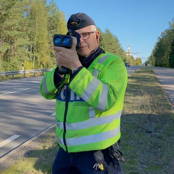 Trafikpolisen Lars Österberg som står bredvid en polisbil och skjuter med laserkikare på förbipasserande bilar.