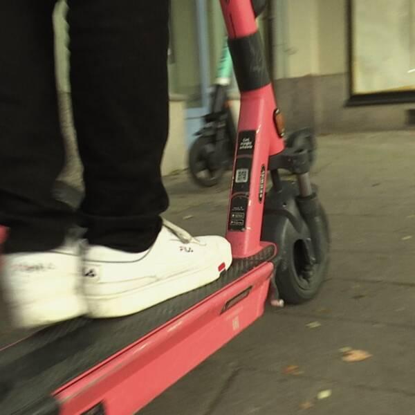 En person sparkar iväg med sin elsparkcykel.