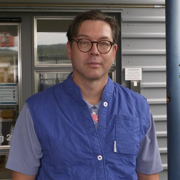 Erik Backhaus i blå väst utanför ingången till infektionskliniken