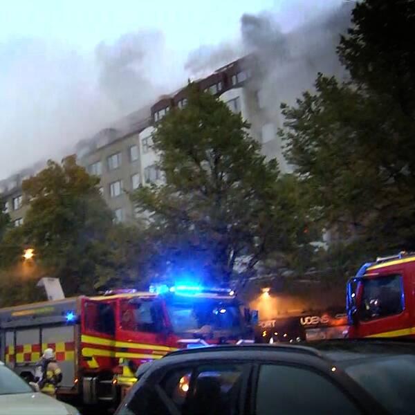 Rök kommer ut ut ett stort flerfamiljshus. Räddningstjänstens bilar står i förgrunden.