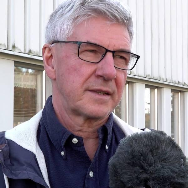 En gråhårig man med glasögon.
