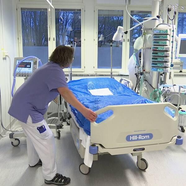 En sjukhussal där en personal flyttar en säng.
