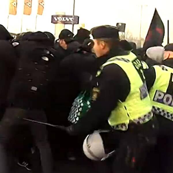 Polis föser tillbaka maskerade demonstranter nära lokalerna där Sverigedemokraterna håller sina landsdagar.