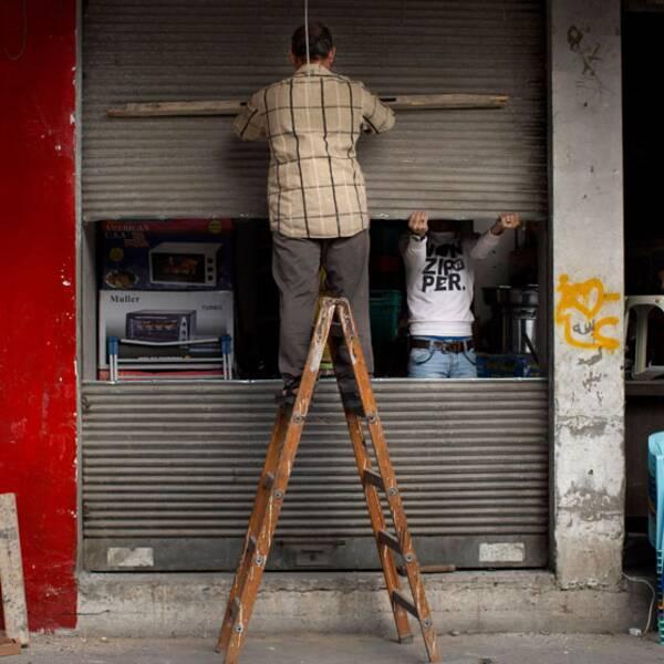 En palestinsk man reparerar sin affär som skadats i den senaste tidens strider.