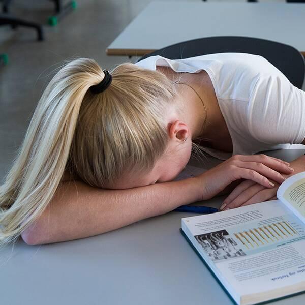 Tonårstjej ligger över bänken i klassrum. Framför henne ligger böcker.