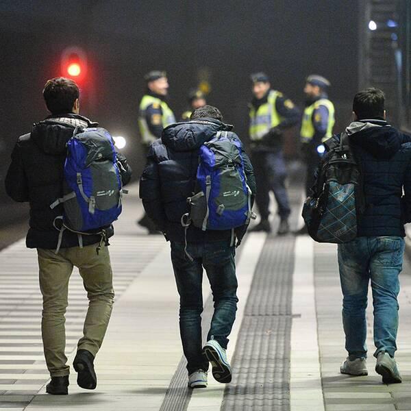 Tre flyktingar och en polis. I bakgrunden ser man fyra poliser.
