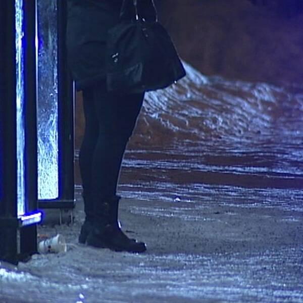 Kvinna väntar vid busshållplats nattetid