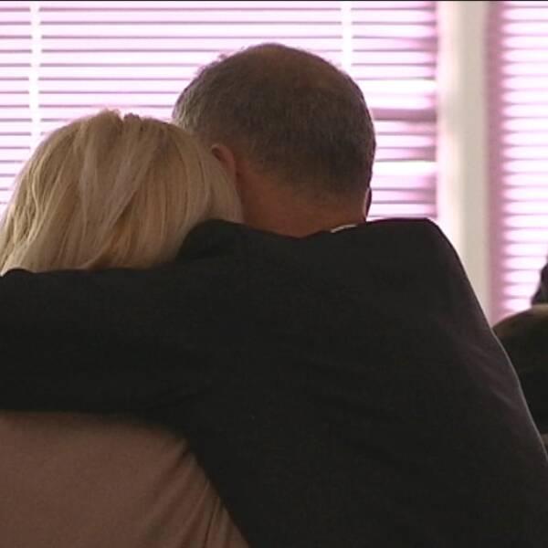 Ett kramade par med ansiktena vända från kameran.