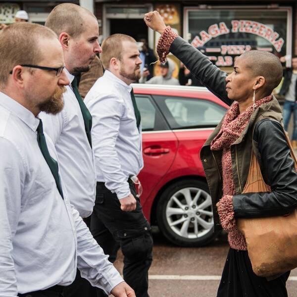 Kvinna står med uppsträckt arm framför första Nordiska Motståndsrörelsen, under första maj i Borlänge 2016.