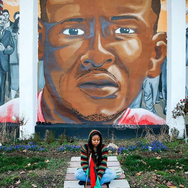 En kvinna sitter framför en väggmålning som föreställer Freddie Gray och som satts upp intill platsen där han greps.