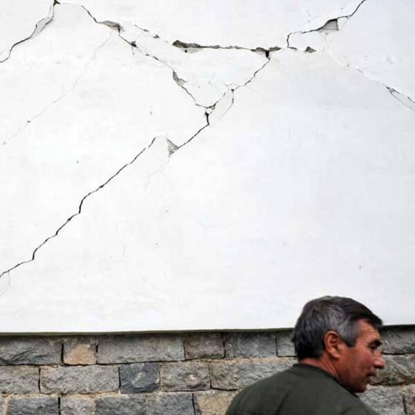 En man framför sitt förstörda hus i byn Rudarci utanför Pernik. AFP PHOTO / NIKOLAY DOYCHINOV