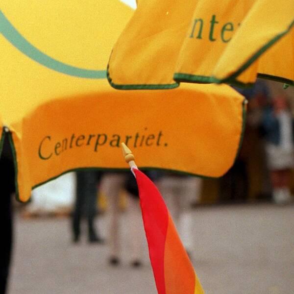 Centerpartiets logotyp på parasoll och en pride-flagga