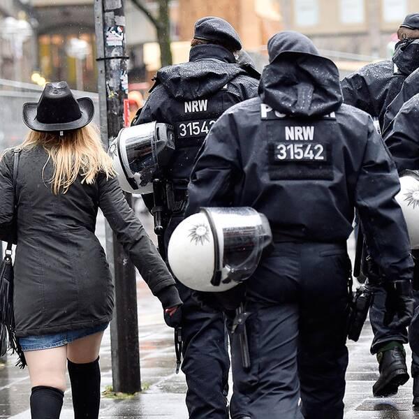 Kvinna tillsammans med poliser i Tyskland.