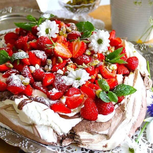 fin tårta med jordgubbar och blommor på maränbotten på gammaldags bricka.