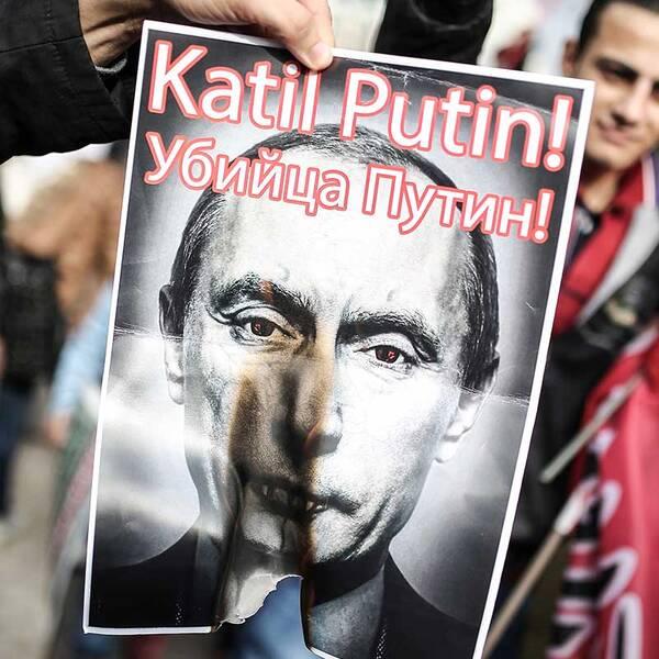 """27 november 2015. En turkisk demonstrant bränner en bild på ryske presidenten Vladimir Putin efter nedskjutningen av ett ryskt bombplan på gränsen mellan Turkiet och Syrien. På bilden står """"Putin mördare"""" på turkiska och ryska."""