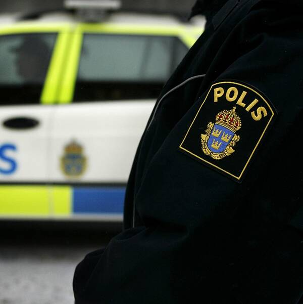 En polisbil och en polis i uniform