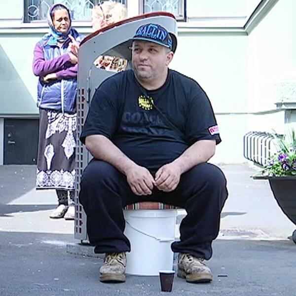 Florin Călin sigger på en pall utanför en affär.