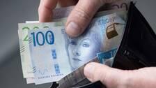 En hand plockar upp nya sedlar ur en plånbok