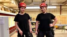 Ellie Klarqvist och Amanda Nordström i svarta byggkläder och röda hjälmar
