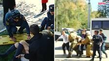 En kvinna ligger på marken med räddningspersonal omkring och ska bäras upp på en bår. Till vänster syns räddningspersonal springa snabbt med en person på bår.