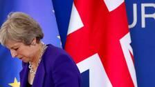 Theresa May tittar ner. I bakgrunden syns Storbritanniens och EU:s flaggor.