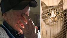 närbild på en gammal man med handen delvis för ansiktet, samt en katt bakom galler