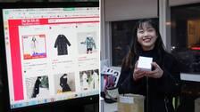 En webbläsare med en webbshop. Till vänster en person som håller upp en paket hon just öppnat.