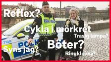 Polisen Tomas Bonn håller i en cykel bredvid reportern Otilia Bogen framför en polisbil vid Eskilstunaån.