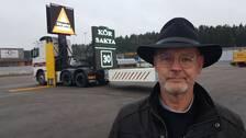 """Man med hatt med stort brätte framför lastbil med digitala skyltar som det står """"Kör sakta"""" på."""