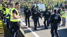 """Polis marscherar genom en korsning som blockeras av """"gula västarna""""."""