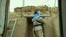 Man tar bort missil från husvägg.