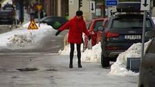 Kvinna i röd jacka som försöker balasera på ishal trottoar.