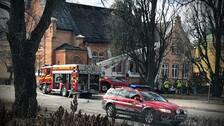 En kyrka, flera brandbilar, en med lång stege och några brandmän.