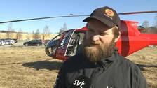 en man i keps och jacka står framför en helikopter på gräsyta, bebyggelse i bakgrunden