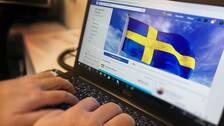 En person skriver på sin laptop. På skärmen syns svenska flaggan som används som bakgrundsbild i Stå upp för Sverige-gruppen på Facebook.