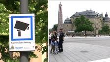 Skylt som varnar för kameraövervakning. Poliser på Järntorget med Örebro slott i bakgrunden