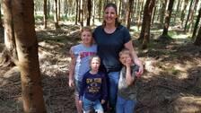Emilie Håkansson tillsammans med sina tre barn i skogen hon äger.