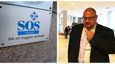 Skylt där det står SOS Alarm, för ett tryggare samhälle och en man i svart kostym med slips