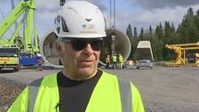 Bild på Rolf Rubensson klädd i varselkläder och bygghjälm framför arbetare som reser ett vindkraftverk i Åskälen