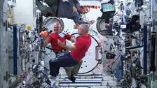 Tre astronauter svävar i luften inne på rymdstationen ISS.