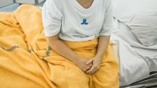 Kvinna som sitter i sjuksäng.