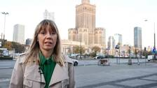 Kvinna i ljust hår framför hög byggnad i östeuropeisk stil.