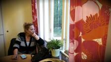 En kvinna sitter vid ett fönster och tittar ut, hon har blont hår uppsatt i en tofs, en grårandig kofta och lutar huvudet i handen. På bordet framför henne ligger hennes mobiltelefon. Utanför syns grönska.