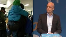 På bilden syns förre statsministern Fredrik Reinfeldt till höger i bild. Till vänster ett barn och flera asylsökande vuxna.